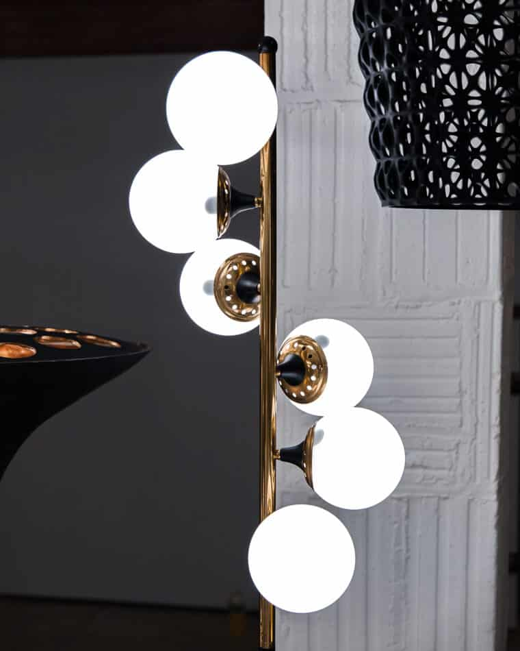 A closeup of a 1950s Stilnovo floor lamp in the installation.