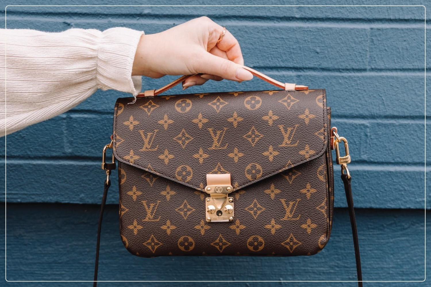 woman's hand holding out louis vuitton purse