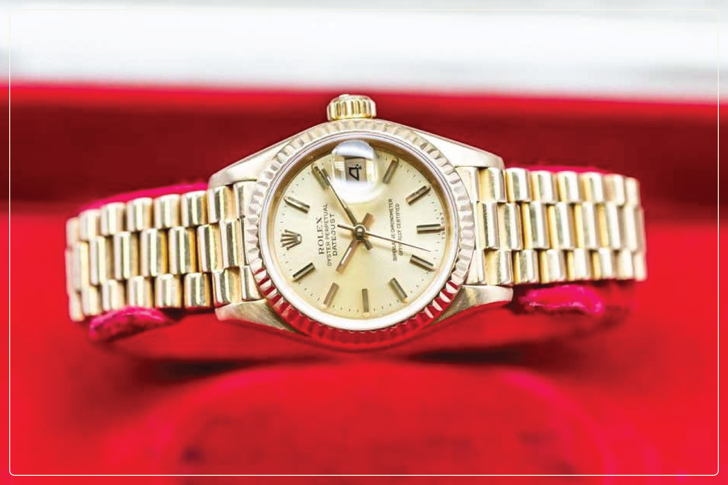 gold rolex sitting on red cushion