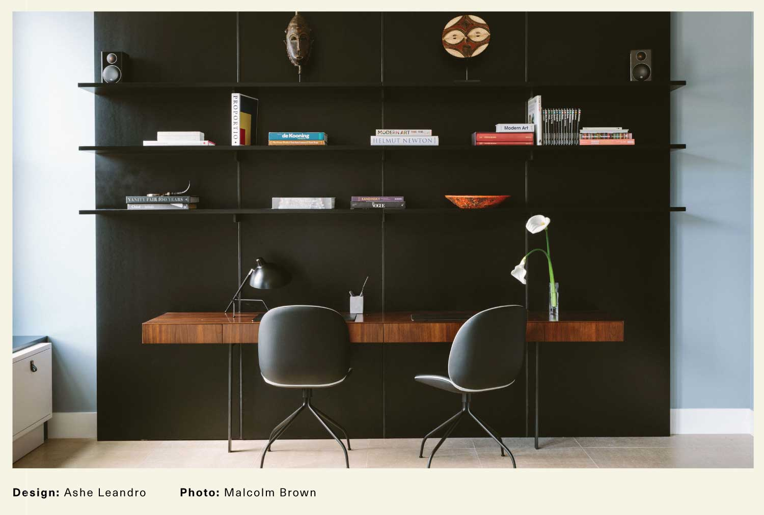 Ashe Leandro interior with contemporary desk against a black wall and a minimal bookshelf