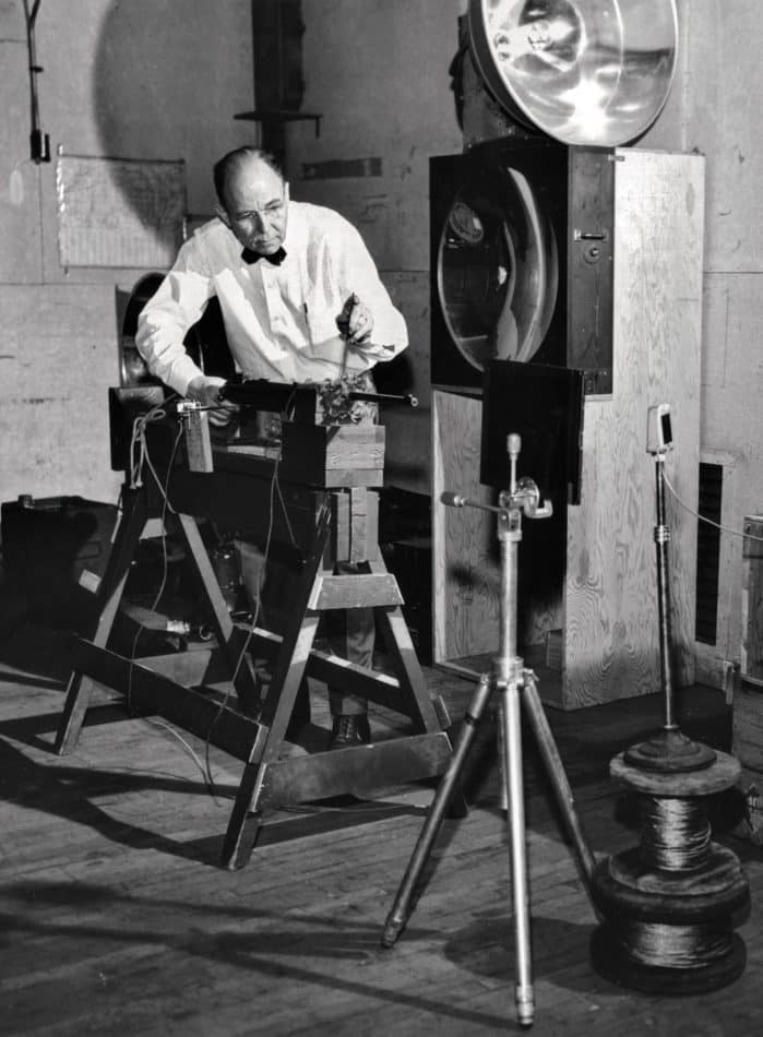 Edgerton setting up a rifle for one of his high-speed photographs of bullets piercing objects.