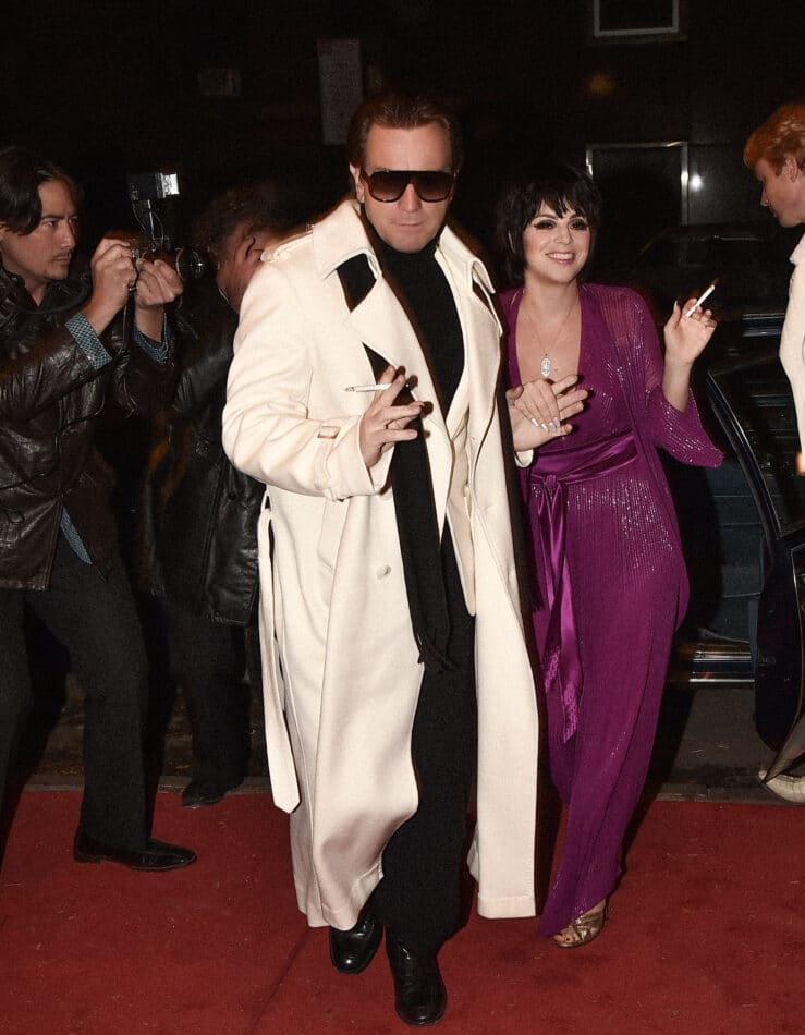 Ewan McGregor as Halston and Krysta Rodriguez as Liza Minelli glide past paparazzi and onlookers to enter Studio 54 in episode four of Halston.