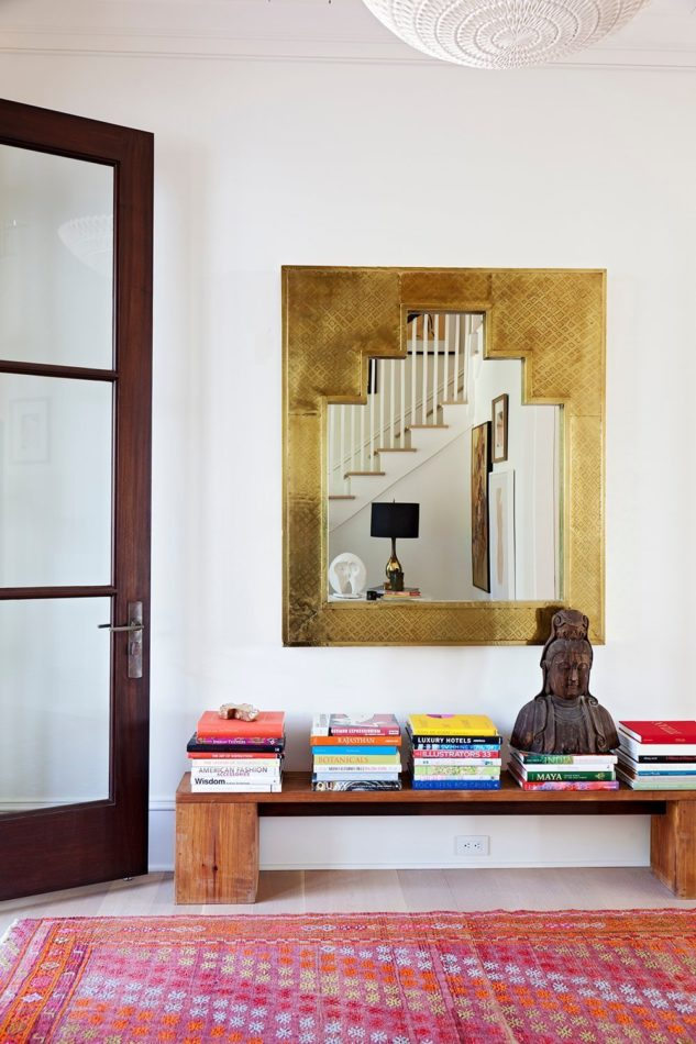 Foyer designed by Angie Hranowsky with a Buddha statue and stacks of books