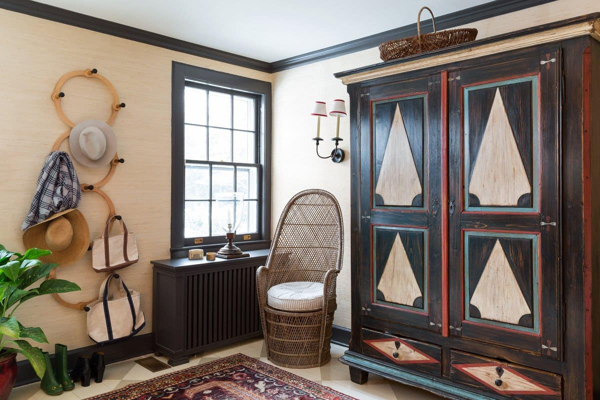 In the entry hall of this Long Island, New York, home, Kemble introduced two rattan pieces — a chair and a basket — to provide visual balance for the unexpected material in an otherwise preppy room.