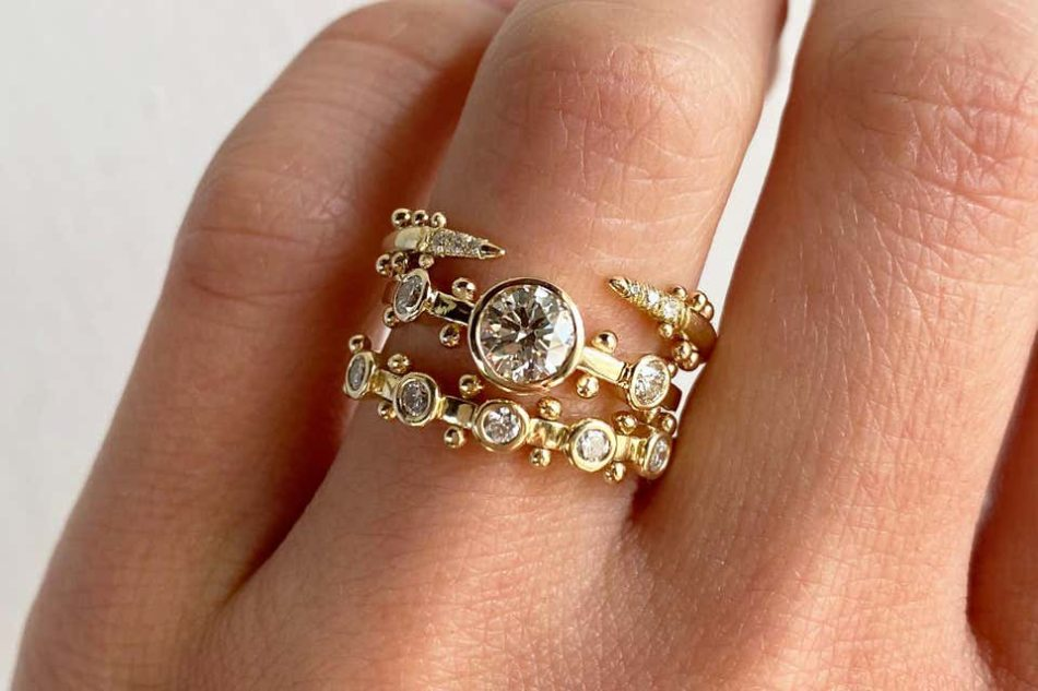 M. Hisae's open stacking ring, white diamond Trinity engagement ring, and Trinity wedding band