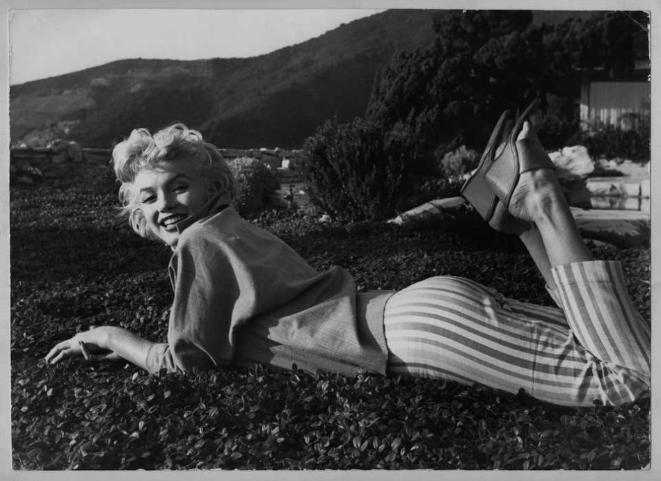 Baron Sterling Henry Nahum Sweet and laughing Filmstar Marilyn Monroe is laying on the green, 1954