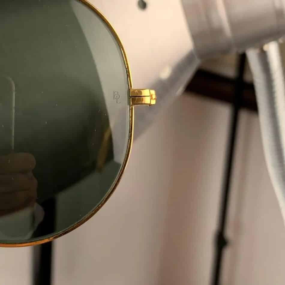 The letters BL etched into the left lens of The Ray-Ban signature logo on the left lens of a pair of late-20th-century Outdoorsman sunglasses offered by Opherty & Ciocci