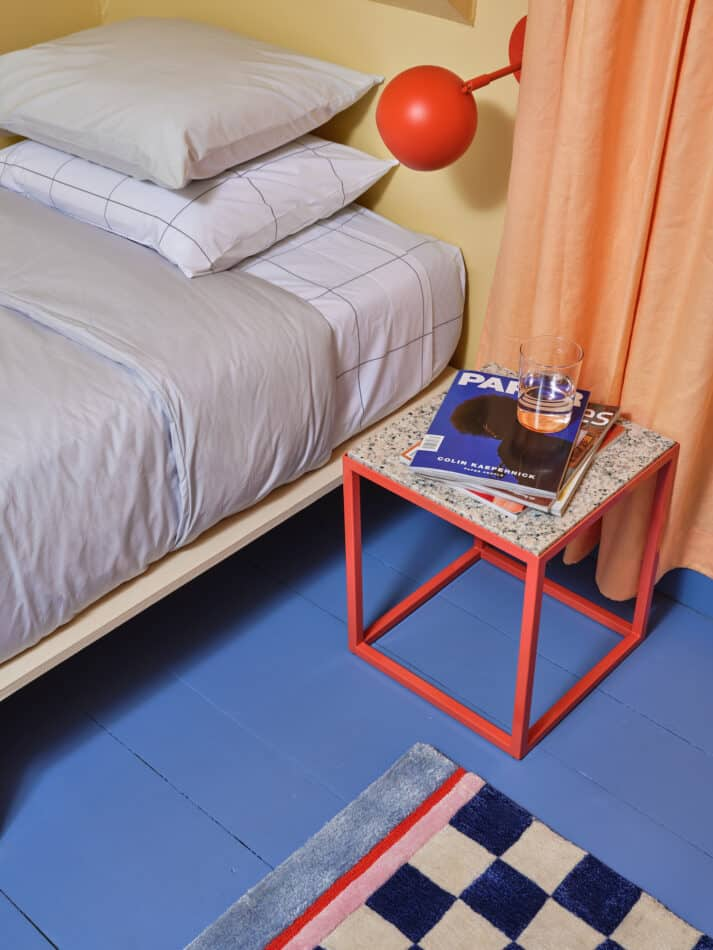 Pieces designed the Hybrid side table and Finish Line rug in this bedroom.