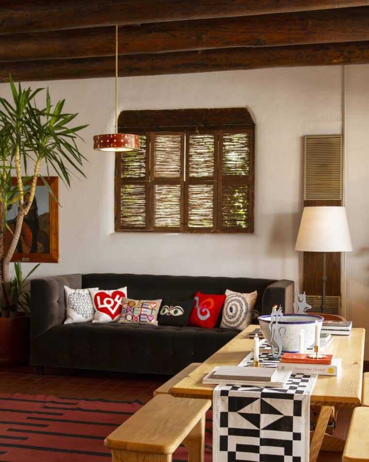 A dining table displays tabletop items and a sofa holds more cushions, including the Love pillow and Green Eyes pillow.