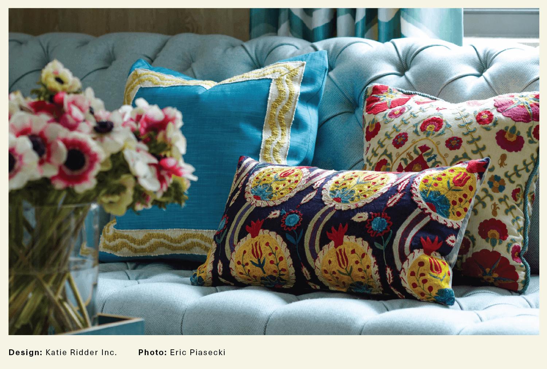 three floral cushions on a blue sofa