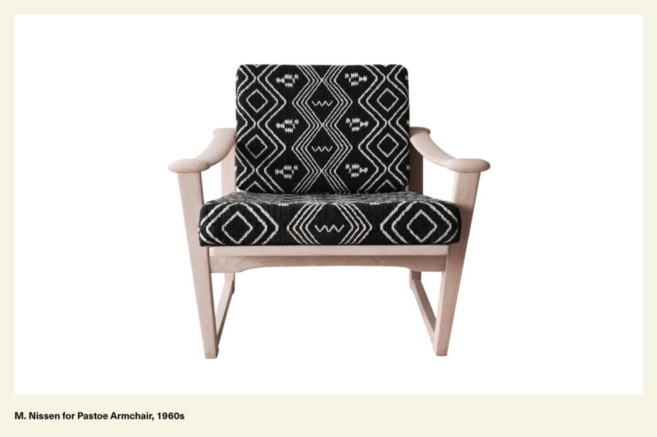 A black and white boho patterned chair with light wood legs