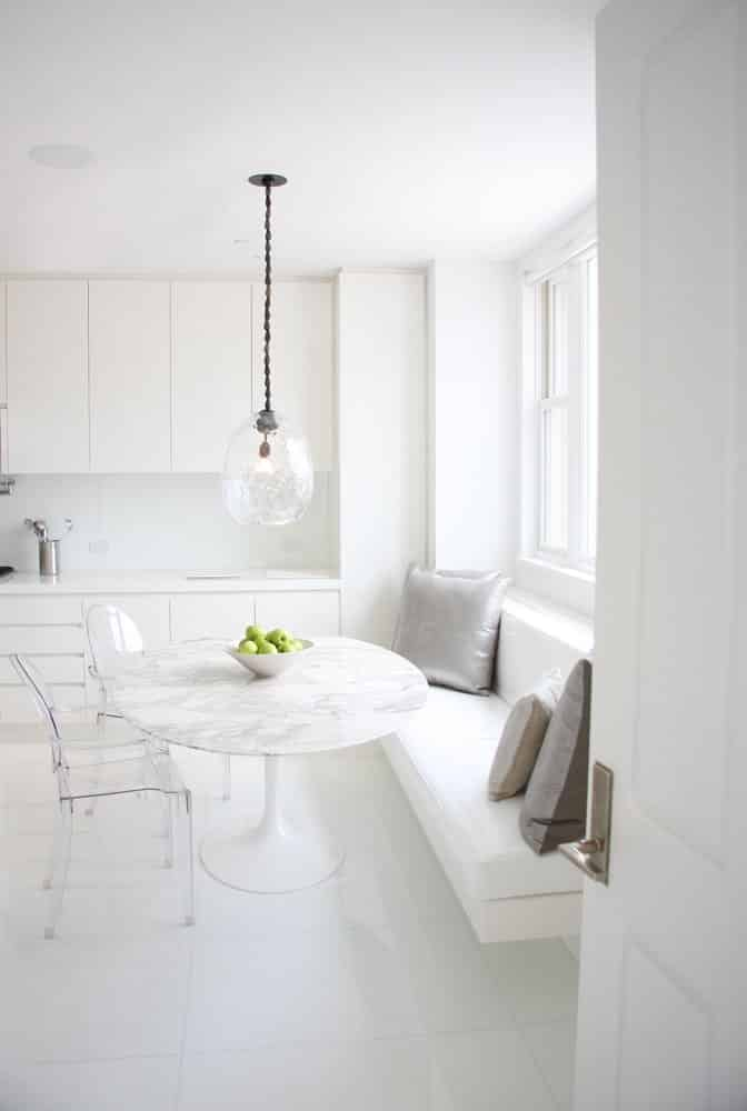 The all-white kitchen of a New York City penthouse by Kelly Behun features lucite chairs around an Eero Saarinen Tulip table. Photo by KBS