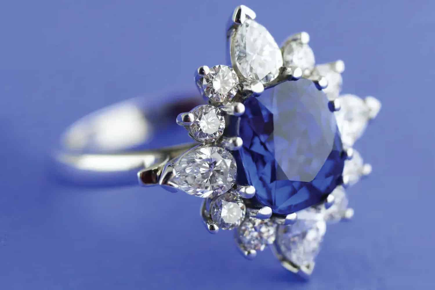 ring with cushion-cut sapphire surrounded by round-brilliant-cut and pear-shaped modified-brilliant-cut diamonds
