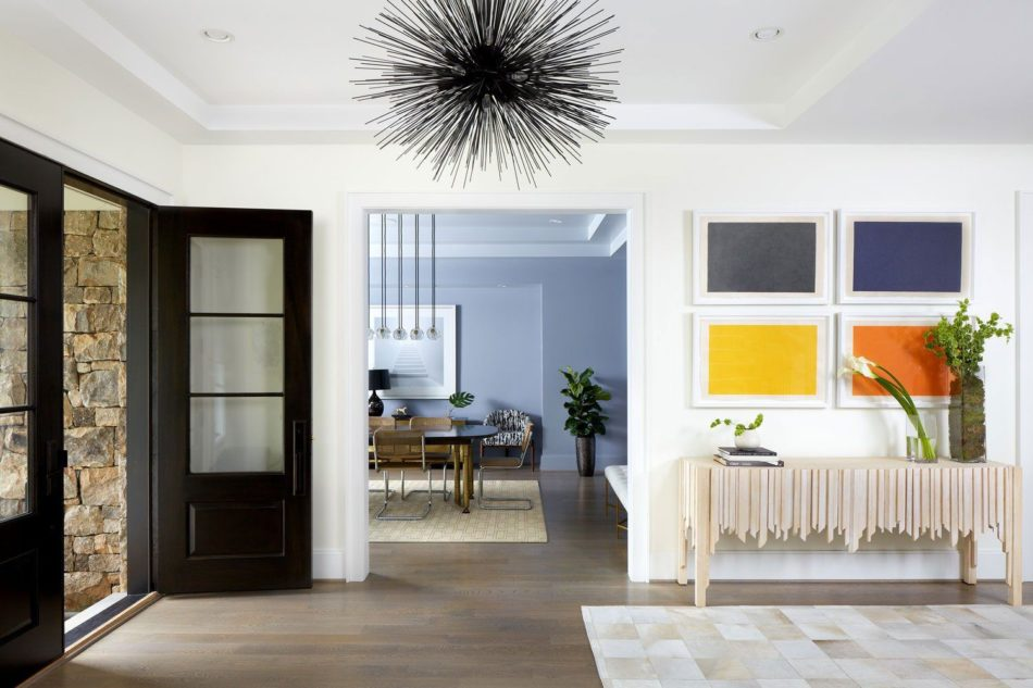 a home entryway with a black door and light fixture, with white walls and colorful art